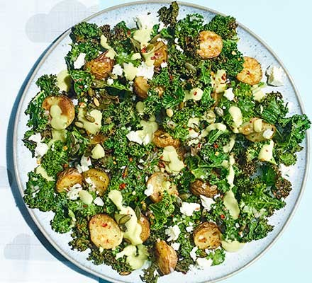 Roasted new potato, kale & feta salad with avocado served on a plate