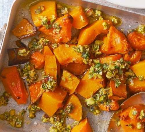 Roasted butternut squash chunks with crushed pistachio on a tray