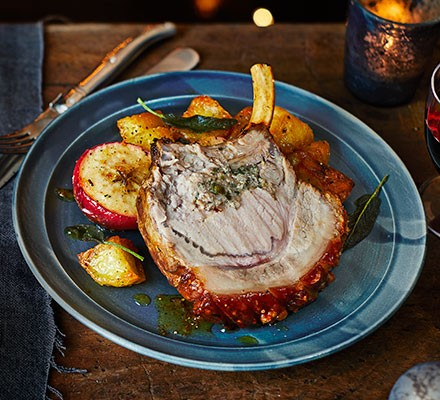 Roast pork with sage & double onion stuffing, baked apples & roasties served on a plate