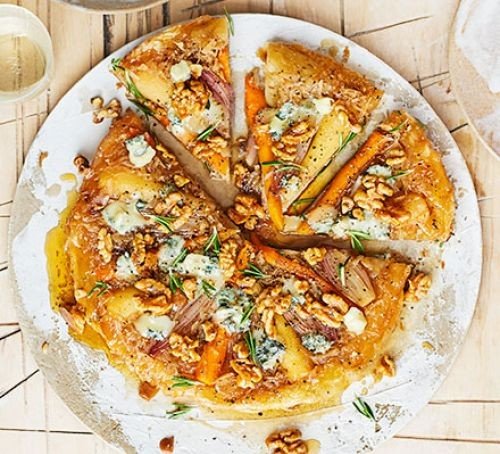 Tart tatin covered in root vegetables, nuts and blue cheese
