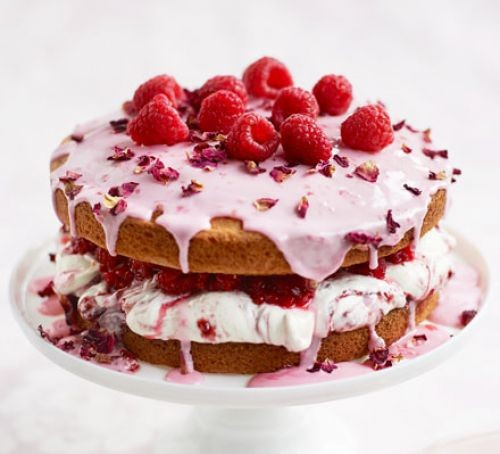Sponge cake topped with pink icing, rose petals and raspberries