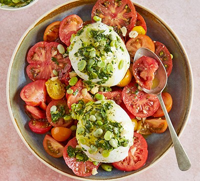 tomato salad with burrata cheese and pesto in bowl
