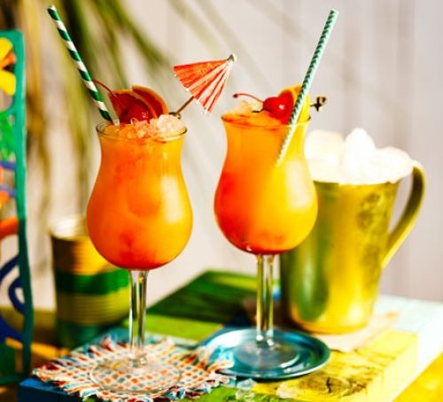 Rum punch in two glasses with cocktail umbrellas and straws