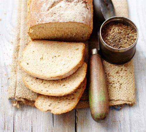 Sliced rye bread loaf on board