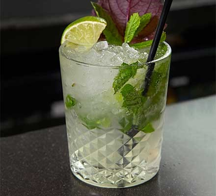 A glass serving a Vietnamese mojito garnished with a slice of lime and a straw