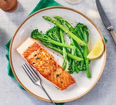 Pan-fried salmon with broccoli and lemon slice on plate
