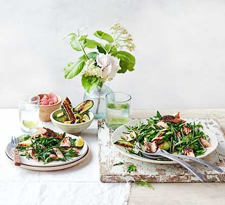Two plates of salmon, samphire & charred cucumber salad on a white table by a flower in a vase