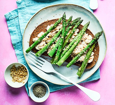 Salmon, sesame & asparagus open sandwich served on a plate with a fork alongside