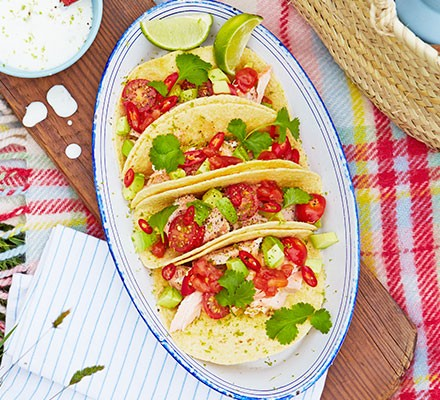 Four salmon tacos with lime dressing on a plate