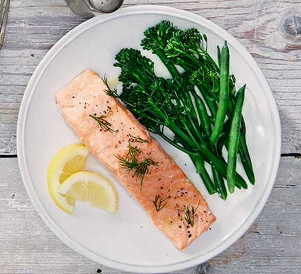 Baked salmon served with broccoli and a slice of lemon
