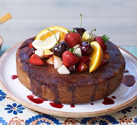 A sangria cake garnished with cherries, strawberries and orange segments