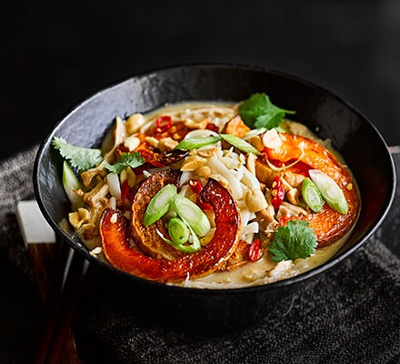 Satay chicken noodle soup with squash in a wok