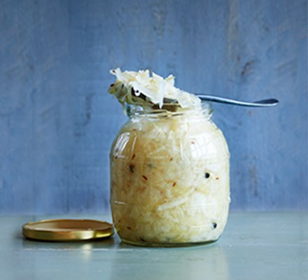 Sauerkraut in a glass jar with spoon