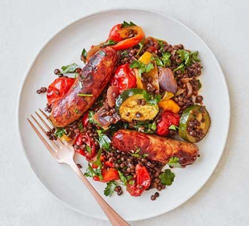 sausages with roasted vegetables and puy lentils on a plate