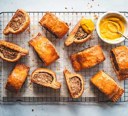 Next level sausage rolls on a wire tray with mustard