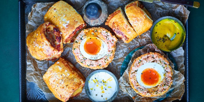 Scotch eggs and sausage rolls on a tray with dips