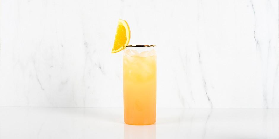 Screwdriver sinaasappelcocktail in hoog glas met gouden rand