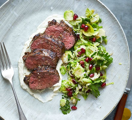 Seared venison slices with sprout & apple slaw on a plate