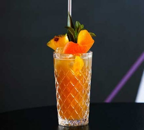 Sherry cobbler in a glass with fruit garnish and straw