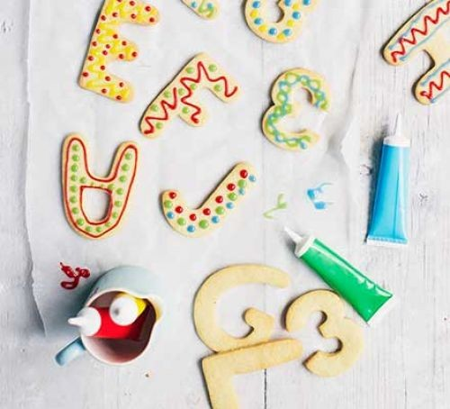 Iced biscuit letters with colourful icing in tubes
