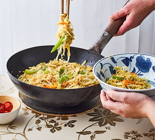 Noodles in wok and bowl