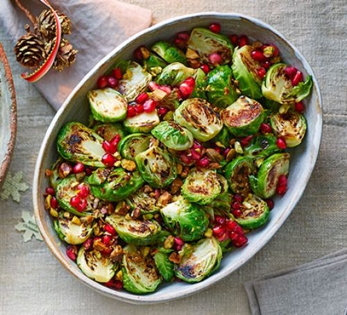 Oval bowl of Brussels sprouts and pomegranates