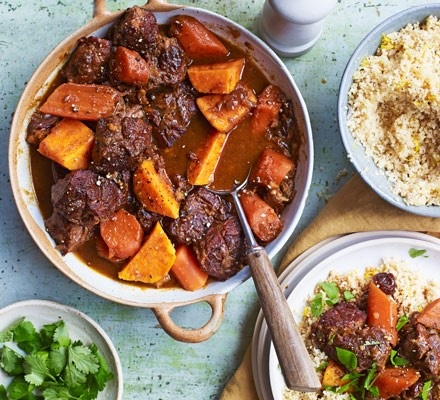 Beef and vegetable stew in pot with ladle and bowls