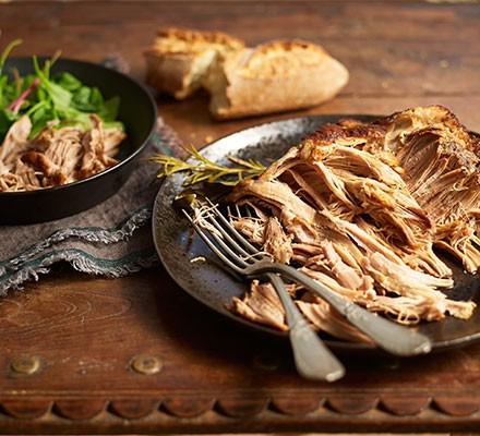 Slow cooker pork shoulder shredded and served on a plate