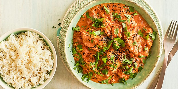 Slow cooker chicken tikka masala in a bowl with rice on the side
