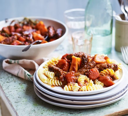 Sausage and carrot stew on pasta on plates