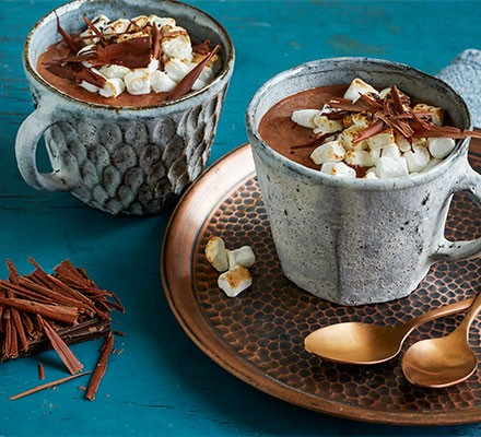 Slow cooker hot chocolate served with marshmallows and chocolate flakes on top