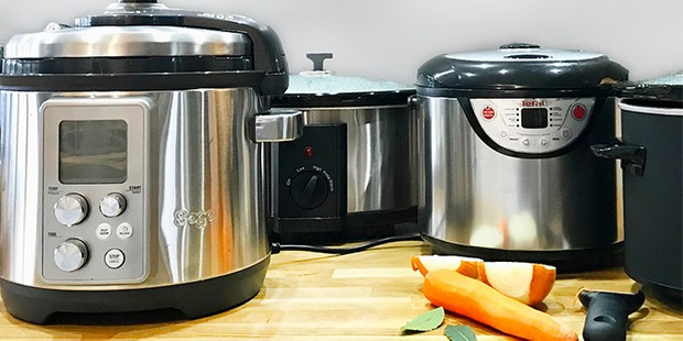 Four slow cookers on a kitchen surface
