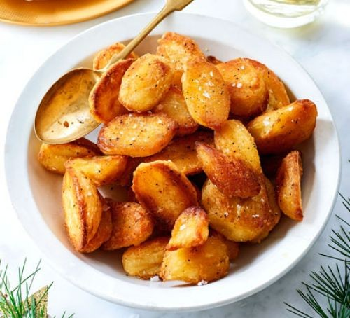 Roast potatoes in a bowl with spoon