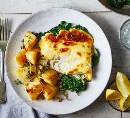 Haddock and potatoes with spinach on plate