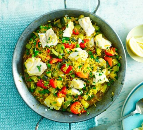 Paella rice dish with cod, tomatoes and herbs
