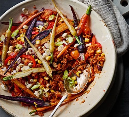 A bowl of spiced rice topped with vegetables