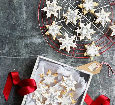 Snowflake biscuits on a wire cooling tray and gift box