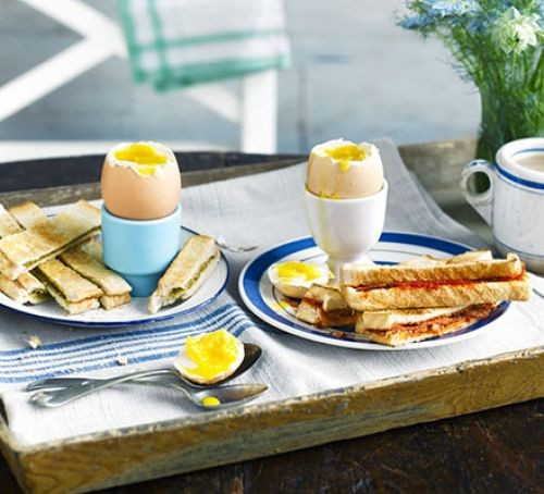 Boiled eggs with soldiers on table