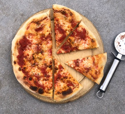 Slices of sourdough pizza next to a pizza cutter