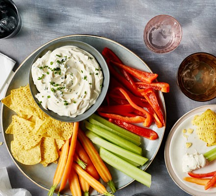 Soured cream in bowl with tortilla chips and crudités