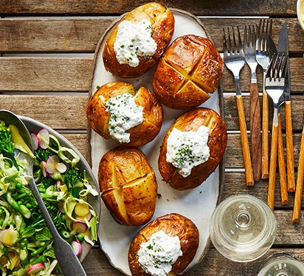 Six soured cream & chive jacket potatoes on a platter