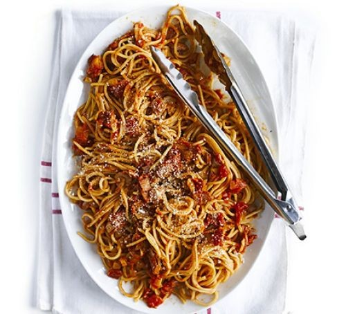 A serving plate of bacon and tomato spaghetti