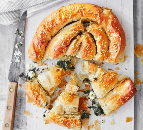 Pastry spanakopita in spiral shape with wedges cut out