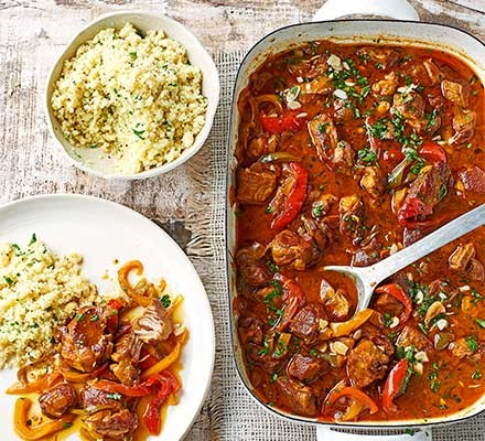 A casserole dish serving Spanish lamb with sherry, honey & peppers