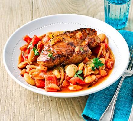 A bowl of bean stew topped with lean pork steak