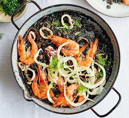 A pan serving Spanish rice with squid, prawn & fennel
