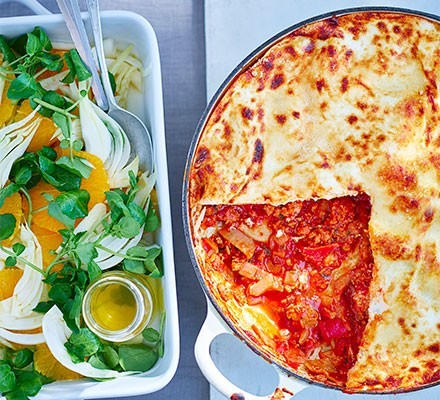 Speedy chorizo ragu lasagne served in a dish with a salad alongside