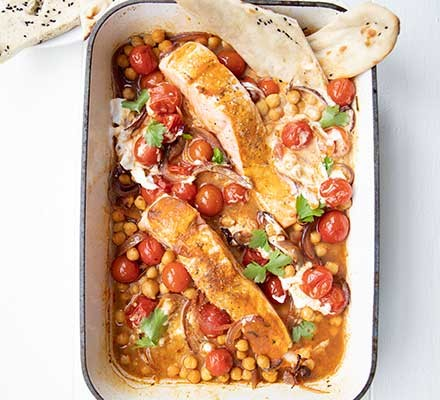 Spiced salmon & tomato traybake served in a roasting tin