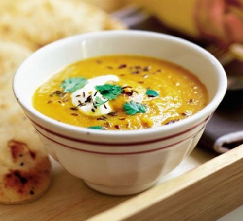 Carrot and lentil soup topped with cumin seeds, yogurt and coriander