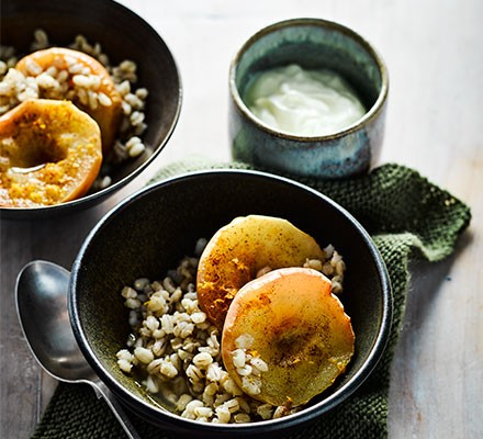 Two bowls serving spiced apples with barley and yogurt on the side